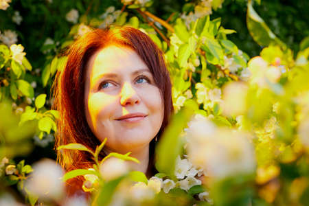 Girl with red hair in a park near a flowering apple tree. Fat woman posing in nature 写真素材