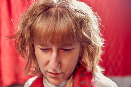 Portrait of serious sad middle-aged woman on red background. Unprofessional female model in the Studio 写真素材