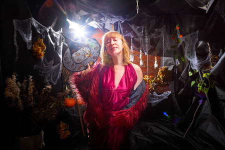 Blonde witch in red dress and black hat in Halloween decoration indoors