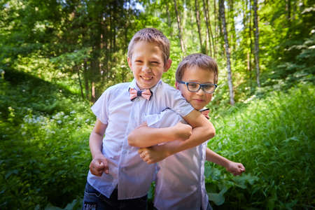 Boys in white shirts and a pink butterfly in nature among the greenery