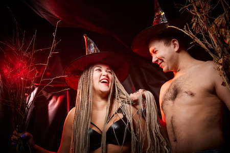 Funny cute couple of man and plump woman with long pigtails in witch hats and broomsticks posing in dark studio. Boy and Girl in love and black background with red light. Halloween photo shoot 写真素材