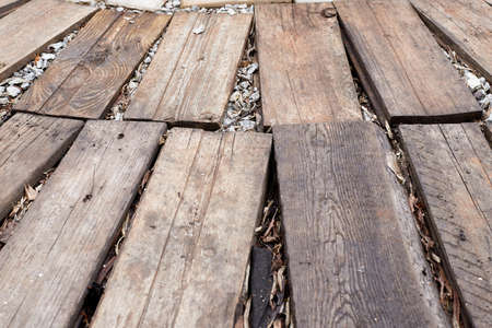 Path made of planks on the ground. Old brown board for background or texture