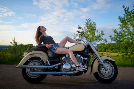 Attractive brunette motorcyclist with motorcycle in a summer evening during sunset. Adventure and travel concept 写真素材