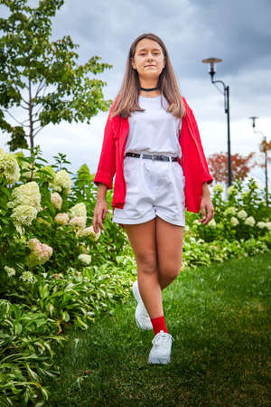 Young girl with long hair on the lawn with green grass and white flowers in a day. Teenager model posing on nature
