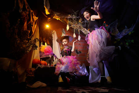 Beautiful brunette mother and cute little daughter looking as witches in special dresses and hats in room decorated for Halloween. Witchcraft and wizardry in carnival. Halloween style photo shoot