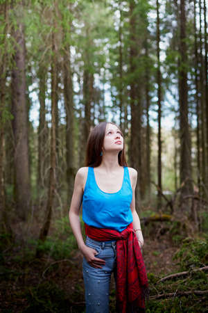 Beautiful young brunette woman with long hair in a forest pines and firs on a summer day 写真素材