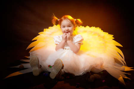 Beautiful cute blonde small girl with white wings looks like an nice young angel during photo shoot in studio with black background and color light
