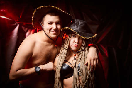 Funny cute couple of man and plump woman with long pigtails in cowboy hats posing in dark studio. Boy and Girl in love and black background with alarming red light