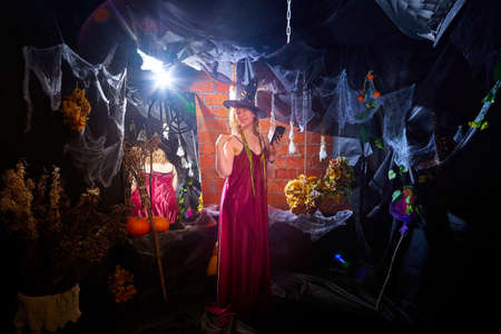 Blonde witch in red dress and black hat in Halloween decoration indoors with cell phone. Woman taking selfie during holiday carnival
