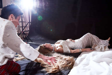 People help model during photo shoot in the studio 免版税图像