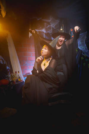Two adult women looking as witches having fun and posing in dark room decorated for Halloween during photoshoot in studio 免版税图像
