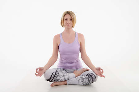 Girl doing yoga in studio with a white background