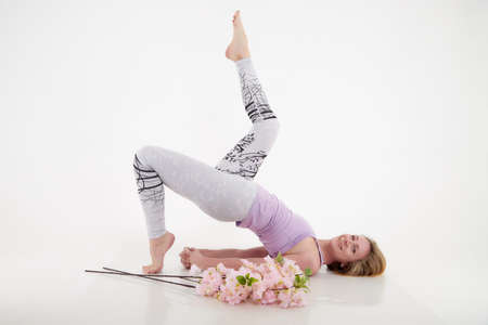 Girl doing yoga with beautiful flowers in studio with a white background