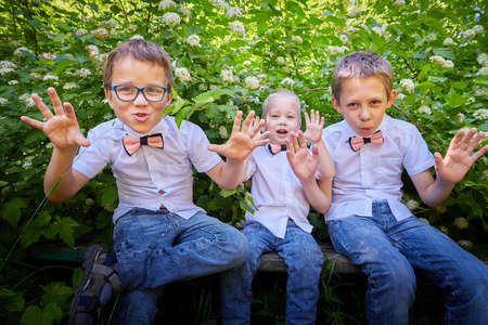 Boys in white shirts and a pink butterfly in nature among the greenery. Funny walk of three brothers in the park or forest 免版税图像