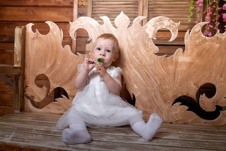 Portrait of little blonde girl in a white beautiful dress. Baby 1 years old in studio during photo shoot 免版税图像