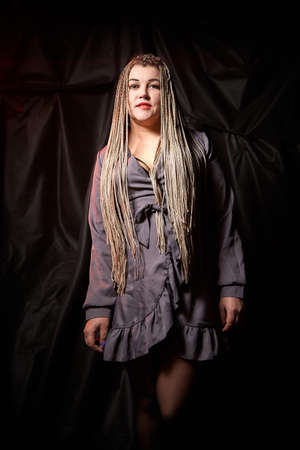 Portrait of a blonde girl with a lot of pigtails on a black background in the studio