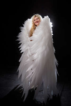 Beautiful blonde girl with curly hair and white wings looks like an nice angel
