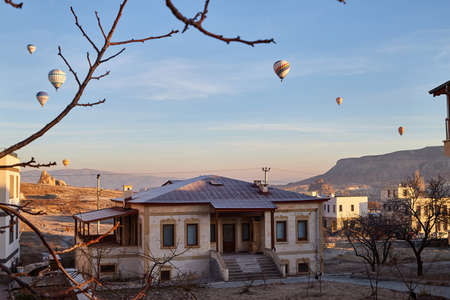 Cappadocia, Turkey - December 20, 2019: Hot air balloons flying in blue sky with white clouds over homes of city Goreme at morning during sinrise. Great interesting attraction for tourists