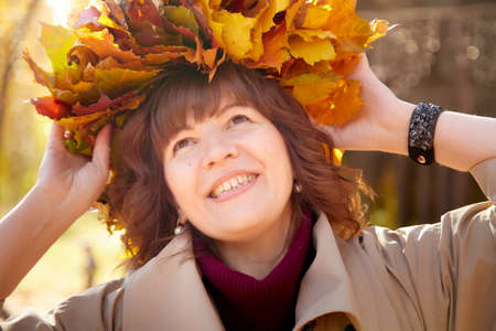 Portrait of mature woman in autumn park and yellow leaves background