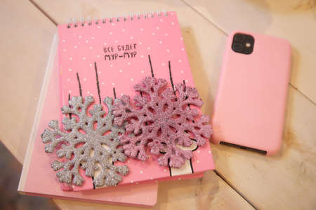 Pink notebook and wood table. Pink cell phone and artificial snowflake near it 免版税图像