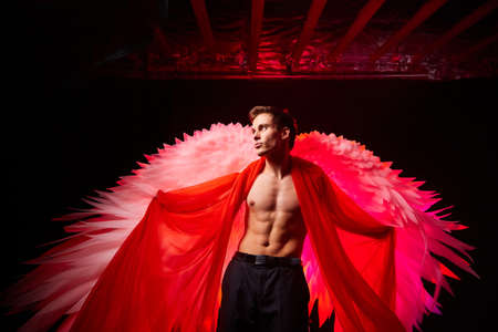 Handsome young athletic man with a bare torso who looks like an angel with white wings. Model dancer posing in dark studio on black background 免版税图像