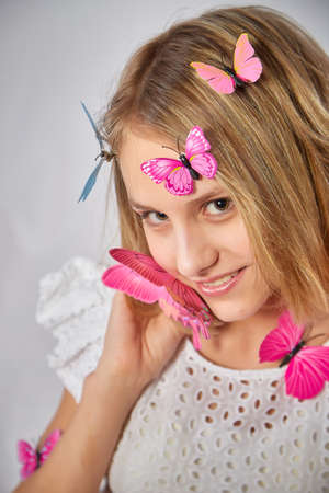Young teen blonde girl with butterflies and white studio background. Spring portrait. Healthy skin and natural makeup for teenage girls