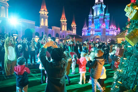 Belek, Turkey - December 18, 2019: Tourists and actors on the street of the city of Belek at night with beautiful color lighting before Christmas. 新闻类图片