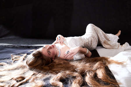 Young attractive girl with long blonde hair and beautiful dress posing lying on floor in studio on dark background. Photo of the beautiful hair of model