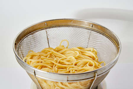 Long spaghetti in an iron colander on white background