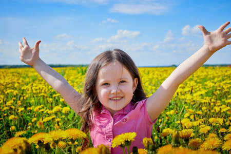 Happy small girl in a field with yellow dandelions. Female child walks in spring in nature in sunny day
