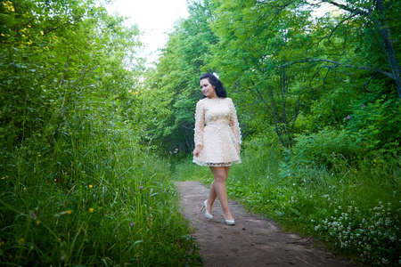 Young beautiful female model in pink dress posing in the summer park or garden with greenery arround her. Girl walking in a forest