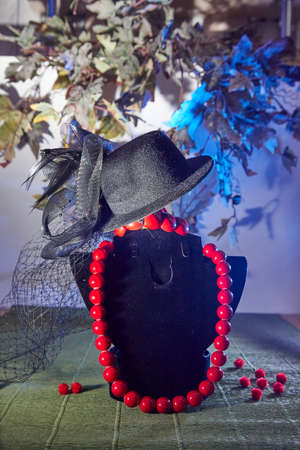 Red beads, bracelet, and an elegant black hat of woman with a veil. The concept of beautiful, elegant life and expensive decoration and dress