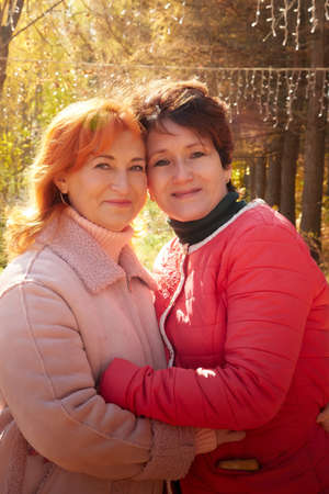 Portrait of two mature woman in autumn park and many yellow leaves background. Two sisters huging each other outdoors
