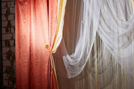 Red stage curtain with light and shadow and white curtains in background
