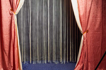 Red stage curtain with light and shadow and white curtains in background Stockfoto - 168421811