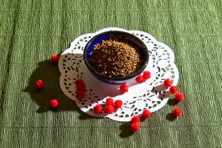 Loose instant coffee in blue beautiful ceramic saucer. Resource for making a delicious coffee drink