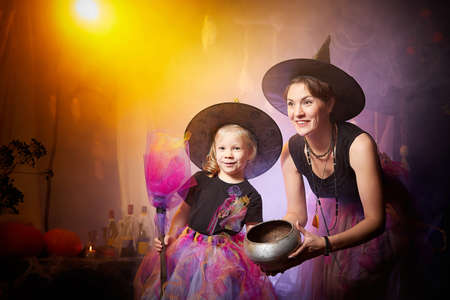 Beautiful brunette mother and cute little daughter looking as witches in special dresses and hats conjuring with a pot in room decorated for Halloween. Halloween style photo shoot Stockfoto - 168421837