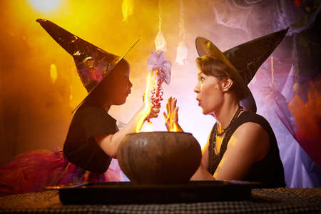 Beautiful brunette mother and cute little daughter looking as witches in special dresses and hats conjuring with a pot in room decorated for Halloween. Halloween style photo shoot Stockfoto