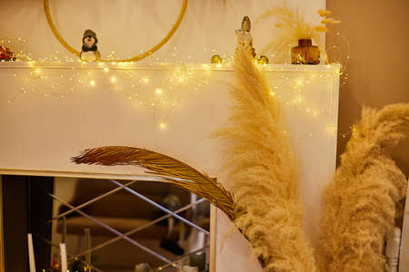 Golden decorations made of plants in the room for celebrating Christmas. Christmas design and bokeh background.