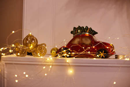 Small toy car on a white shelf with glowing garlands at Christmas
