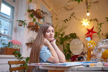 Kirov, Russia - December 17, 2020: Girl with long hair in room with a lot of things and picture. Portrait of a young artist drawing the picture in cozy house Stockfoto