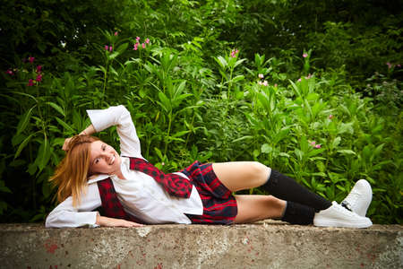 Young girl with short hair in school checkered uniform outdoors