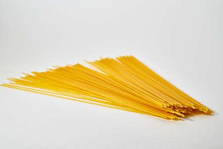 Yellow long uncooked spaghetti close-up on white background Stockfoto