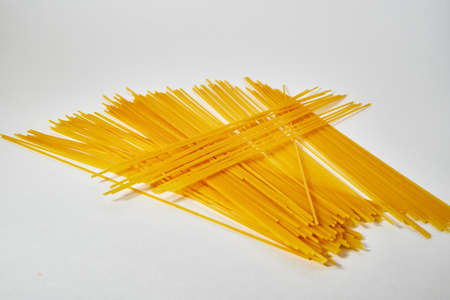 Yellow long uncooked spaghetti close-up on white background Stockfoto