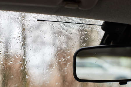 Car windshield with rain drops and the rear view mirror. Blurred trees outside the window on a rainy autumn day Stockfoto