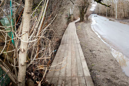 A wooden sidewalk goes through muddy wet countryside road. A path on wet clay