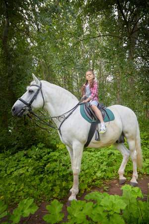Teenage girl and a horse in nature among green trees