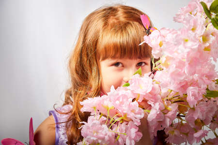 Young girl with blonde curly hair with a butterfly in the studio on a white background. Child posing during a photo shoot. The concept of spring, summer, childhood, happiness