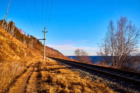 Circum Baikal railway running along the shore of Lake Baikal on an autumn sunny day with yellow landscape around