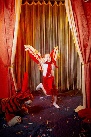 Small girl during a stylized theatrical circus photo shoot in a beautiful red location. Young model posing on stage with curtain